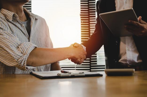 良い仕事 - モバイルタブレットと若い従業員と握手を使用してスーツのビジネスマンチームリーダー