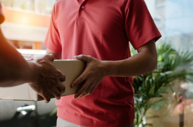 Умный служащий службы доставки на дом в красной форме передает коробки с посылками получателю и клиенту молодого человека