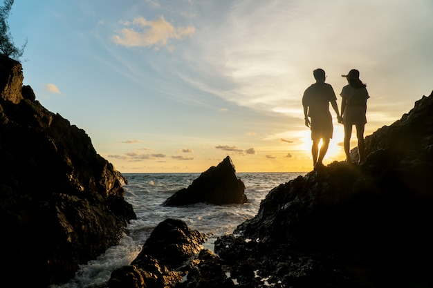 カップルはビーチの夕日に旅行します。