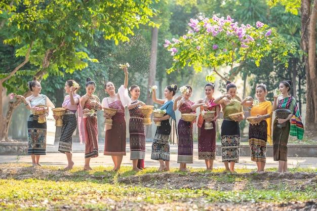 Красивая лаосская девушка в родном платье, плещущая воду во время традиционного лаосского фестиваля вьентьян