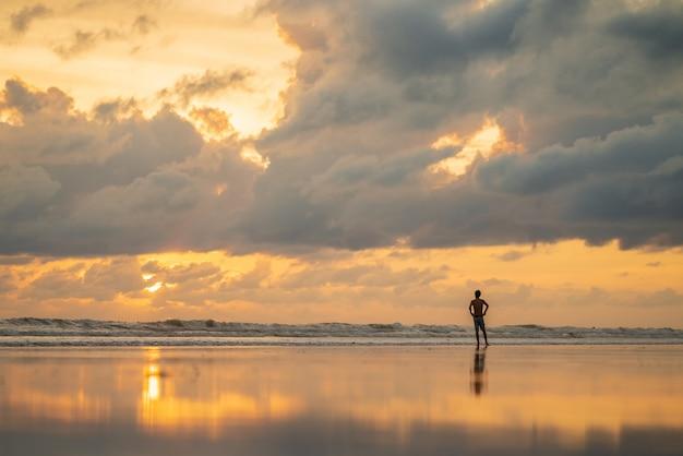 日没時に白い砂のビーチで一人の男