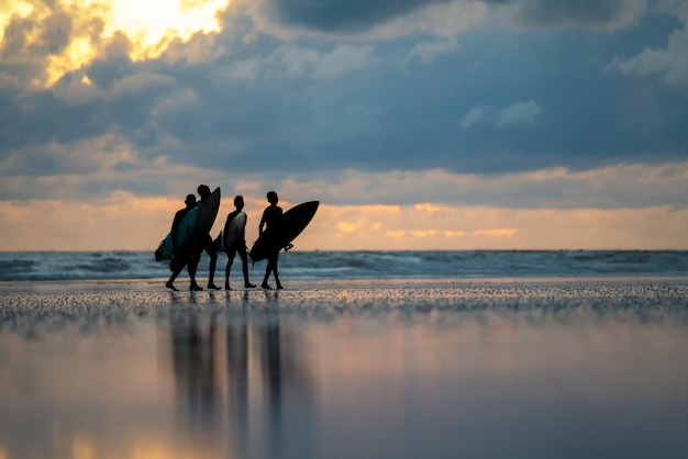 海岸で彼の手でサーフィンを持つ男