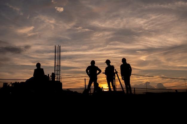Силуэт группы рабочих, работающих на строительной площадке.