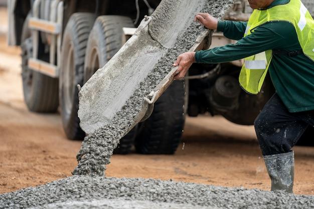 道路建設現場で濡れたコンクリートを注ぐ建設労働者
