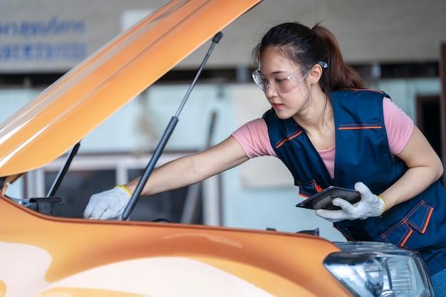 Девушка инженер-механик, работающая на транспортном средстве в гараже или на службе у женщин