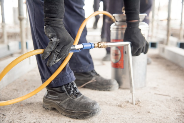 害虫のコントロールの労働者の手をキャビネットに殺虫剤をスプレーするためのスプレーヤーを保持