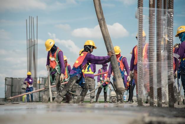 Строитель, заливающий бетон