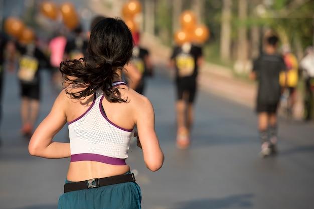 女性が走っている。女性ランナーのジョギング、マラソンのトレーニング。