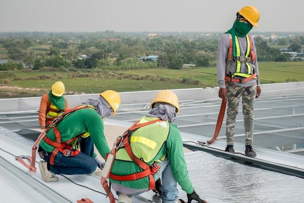 安全産業と金属産業の労働者に働く安全ラインを着て建設労働者