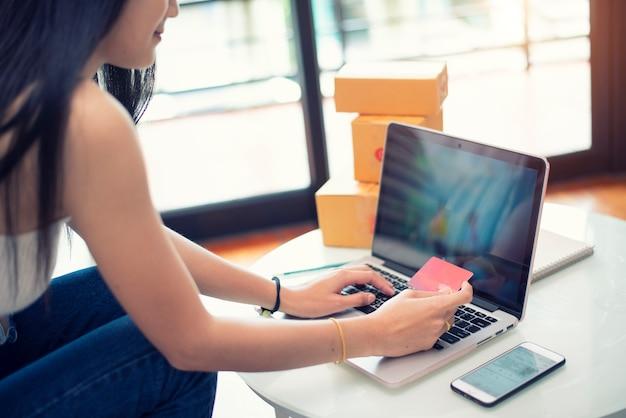 Молодая женщина, платя покупки онлайн с кредитной картой дома