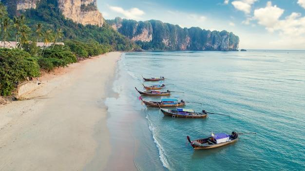 美しいクリスタルクリアな水とロングテールボートで白いビーチの空撮