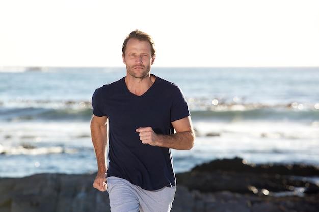 ビーチの外で走っているハンサムな男