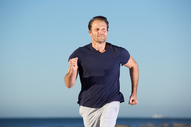 海で屋外で走っているフィットネスマン