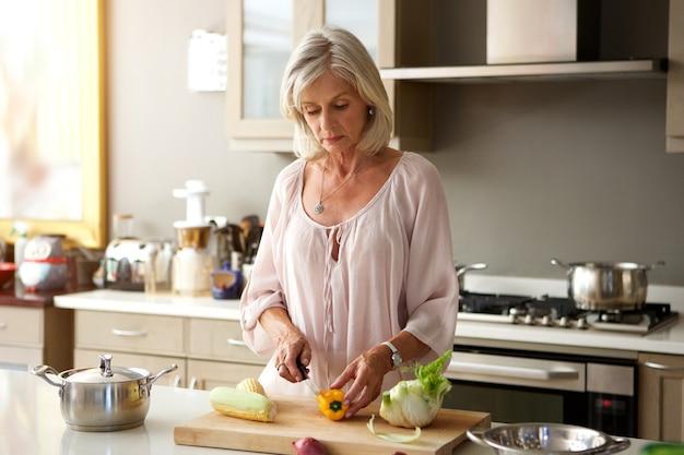 健康的な食事を準備するキッチンの高齢の女性