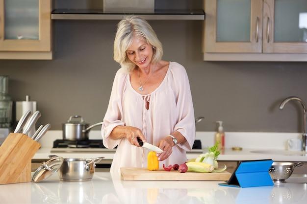 キッチンカット野菜で幸せな年配の女性