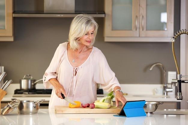 タブレットでレシピを読んでいるキッチンの年上の女性