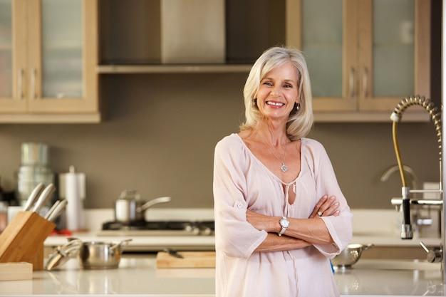 現代のキッチンに立っている老婆
