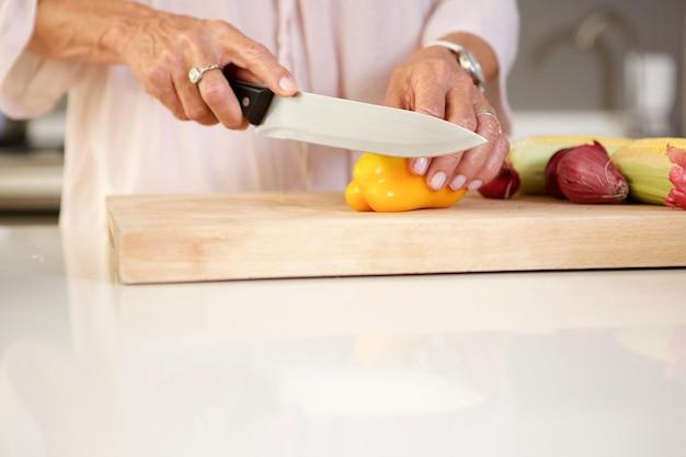 キッチンで新鮮な野菜を切る高齢の女性