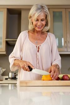 新鮮な野菜を切る台所で幸せな年上の女性