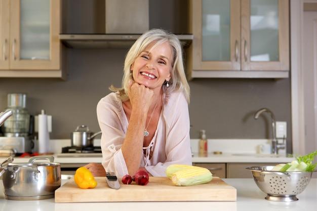 新鮮な野菜とキッチンカウンターに傾いている古い魅力的な女性