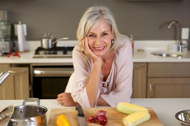 新鮮な野菜とキッチンカウンターに傾いている古い美しい女性
