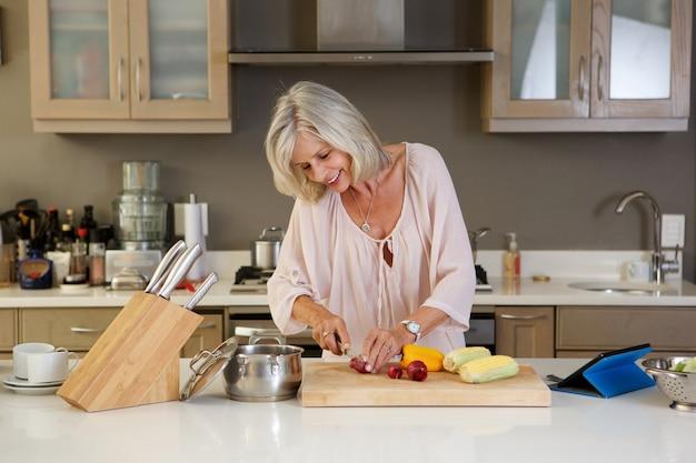 健康的な新鮮な野菜を切る台所の美しい高齢の女性