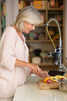 現代のキッチンで野菜を切る高齢の女性