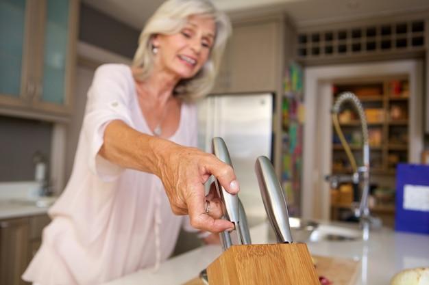 幸せ、古い、女、台所、ナイフ、ブロック