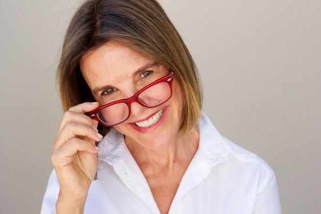眼鏡を持っている幸せなビジネス女性