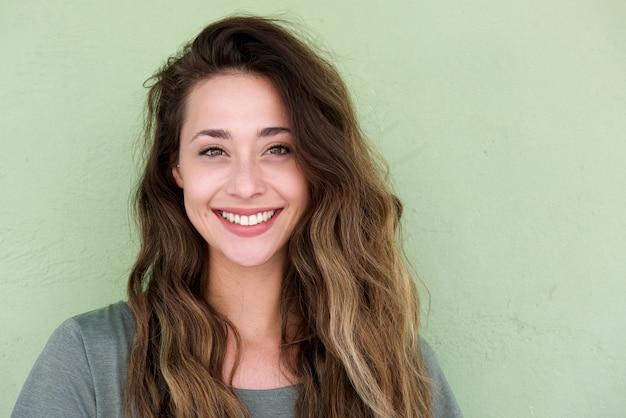 緑色の背景に若い幸せな女性
