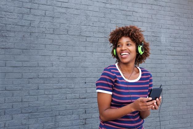 携帯電話とヘッドフォンで音楽を聴く幸せなアフリカの女性の肖像