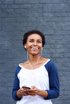 イヤホンと携帯電話で音楽を聴く若い笑顔の女性