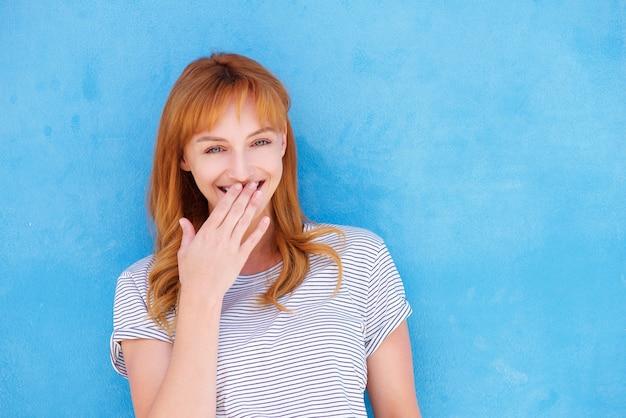 青い壁に向かって口に手を笑う幸せな女性