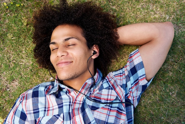 音楽を聴く草の上に横たわっている若い男