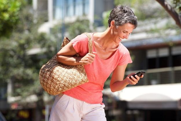 屋外で携帯電話で歩く幸せな女性