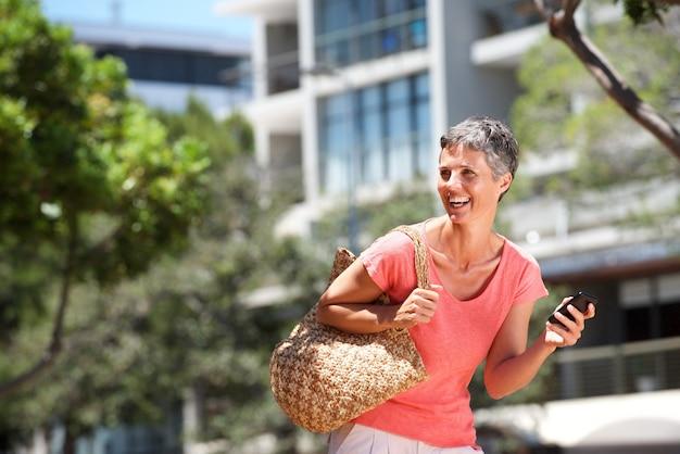 携帯電話で外を歩く幸せな女性
