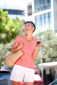 携帯電話で外に笑って歩く高齢の女性
