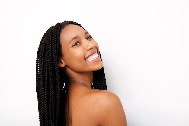 白い背景に笑って編み込まれた髪と朗らかな若いアフリカの女性