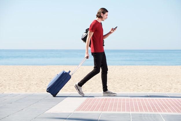 スーツケースと携帯電話で海を歩く笑顔の男の全身の肖像画