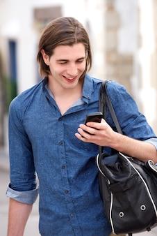 スマートフォンとバッグを持っている長い髪のハンサムな男