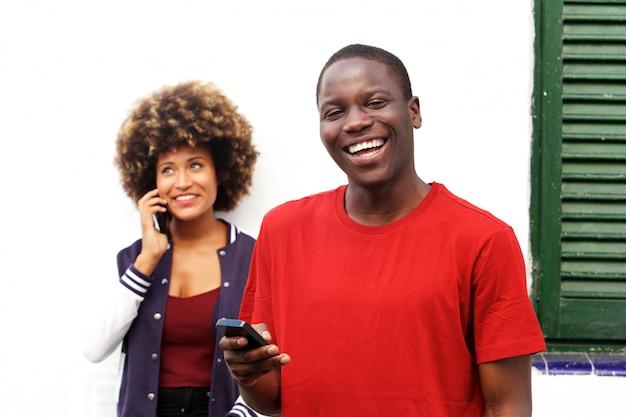 携帯電話と女性は、バックグラウンドで電話をかけて笑っている幸せな男