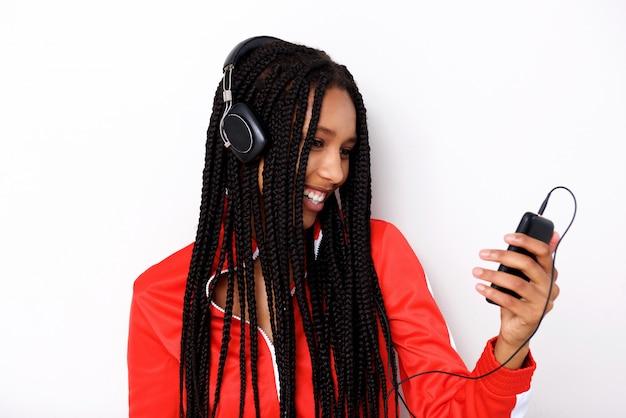 携帯電話とヘッドフォンで若いアフリカの女性が音楽を聴くクローズアップ