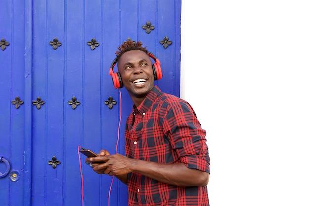携帯電話とヘッドフォンで笑っている幸せなアフリカの男