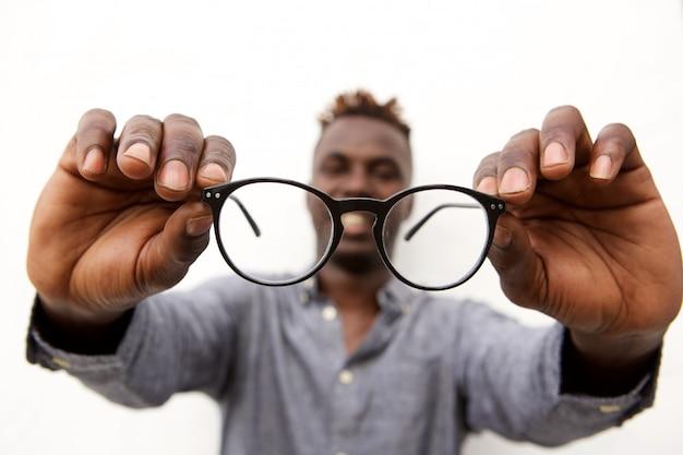眼鏡のペアを保持している男性の手のクローズアップ