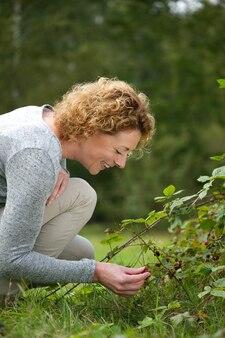 森の果実を摘み取る笑顔の女性