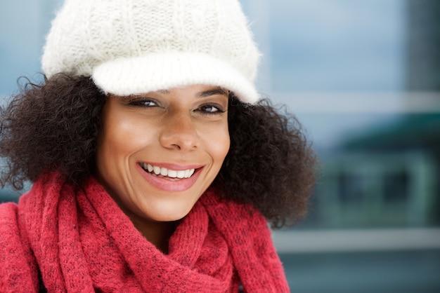 冬の帽子とスカーフで笑う魅力的な黒人女性