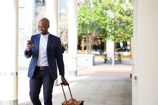 バッグと携帯電話で旅行しているビジネスマン