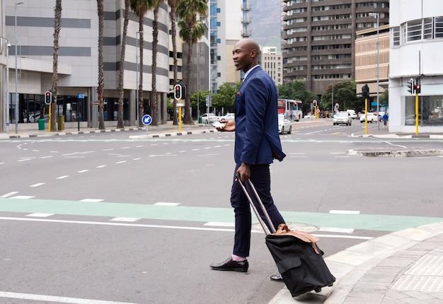 都市でプルバッグで歩くビジネスマン