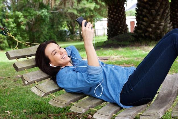 ハンモックで携帯電話でリラックスして笑顔の女性