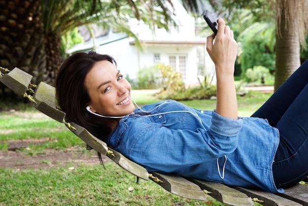 女性は、携帯電話とイヤホンで屋外でリラックス